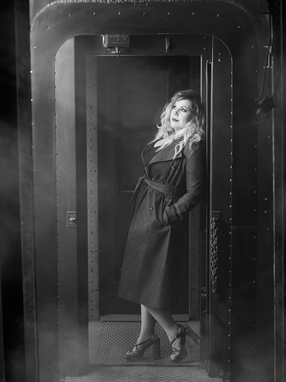Black and white photo of Kirsten Vangsness of Criminal Minds in trench coat.