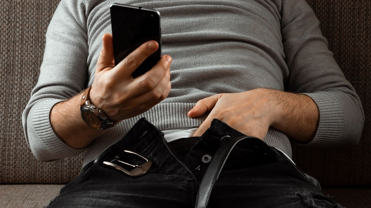 man with hands down pants looking at his phone