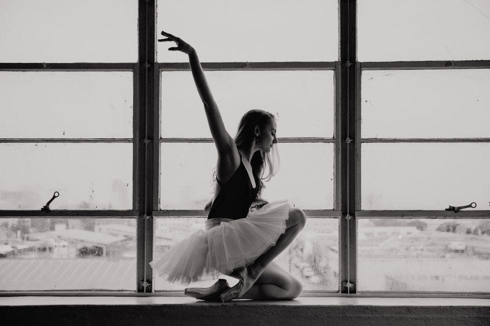 Black and white photograph of Lebowski in a black leotard and white tutu kneeling against a large window in profile. She has one arm lifted.