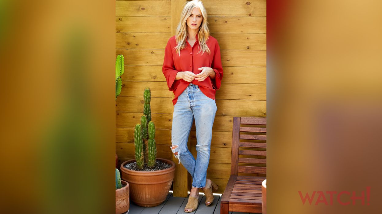 Emily Wickersham leans against a wall wearing a red shirt and ripped blue jeans.