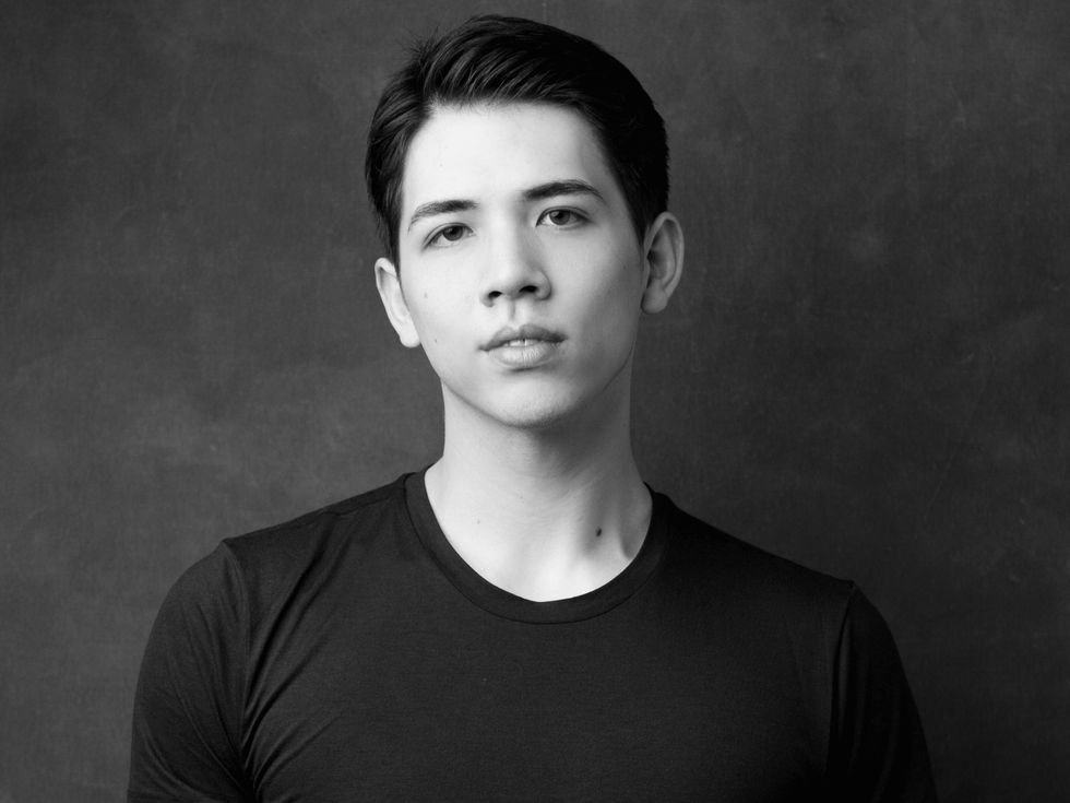 William Yamada is shown from the chest up in a black and white portrait, looking directly at the camera with a small smile. He wears a lack T-shirt and has short dark hair and dark eyes.