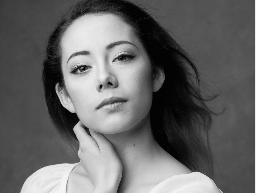 Emily Suzuki is shown from the shoulders up in a black and white portrait, looking directly at the camera with a small closed smile. Wearing a white scoop-neck shirt, she touches her neck with her left hand as her dark hair blows back behind her.