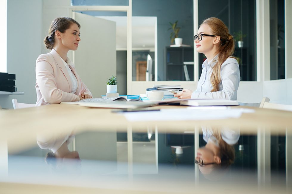 """Professional woman practices her answer to the interview question, """"Tell me about a time you went above and beyond?"""""""