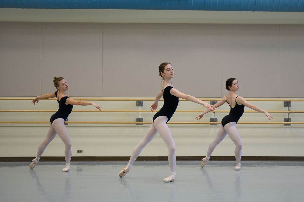 Three ballet dancers take class in black camisole leotards, pink tights and pointe shoes. They are standing in tendu crois\u00e9 derri\u00e8re, with their left leg in pli\u00e9 and their arms in fourth position arabesque.