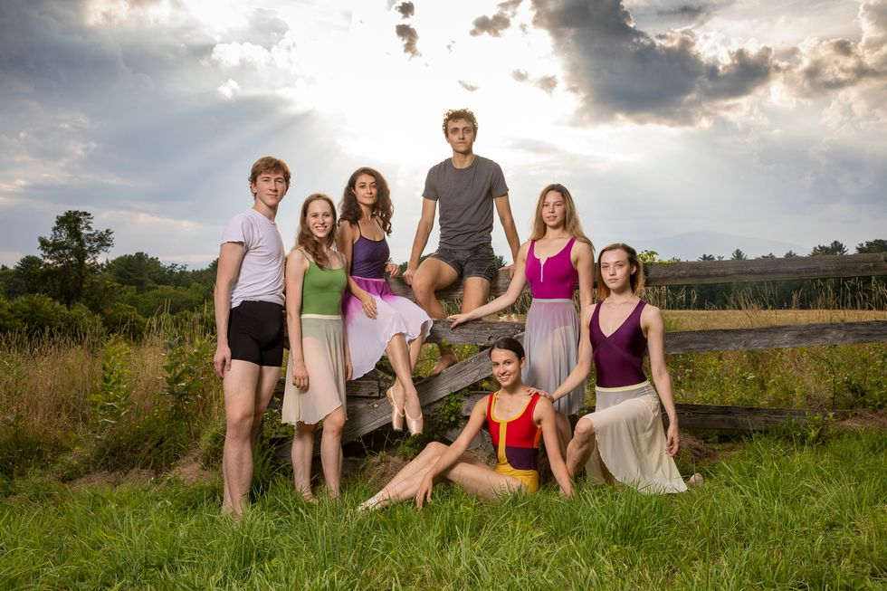 A group of seven ABT Studio Company members pose outside in a field, with two sitting on a gray wooden fence and the rest arranged around them. The two men wear shorts and T-shirts, while the women wear brightly colored leotards and knee-length ballet skirts.