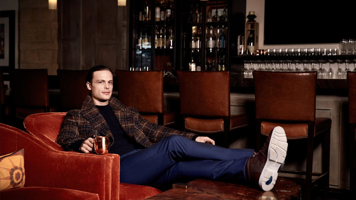 \u200bMatthew Gray Gubler of Criminal Minds lounging in armchair at the a bar.