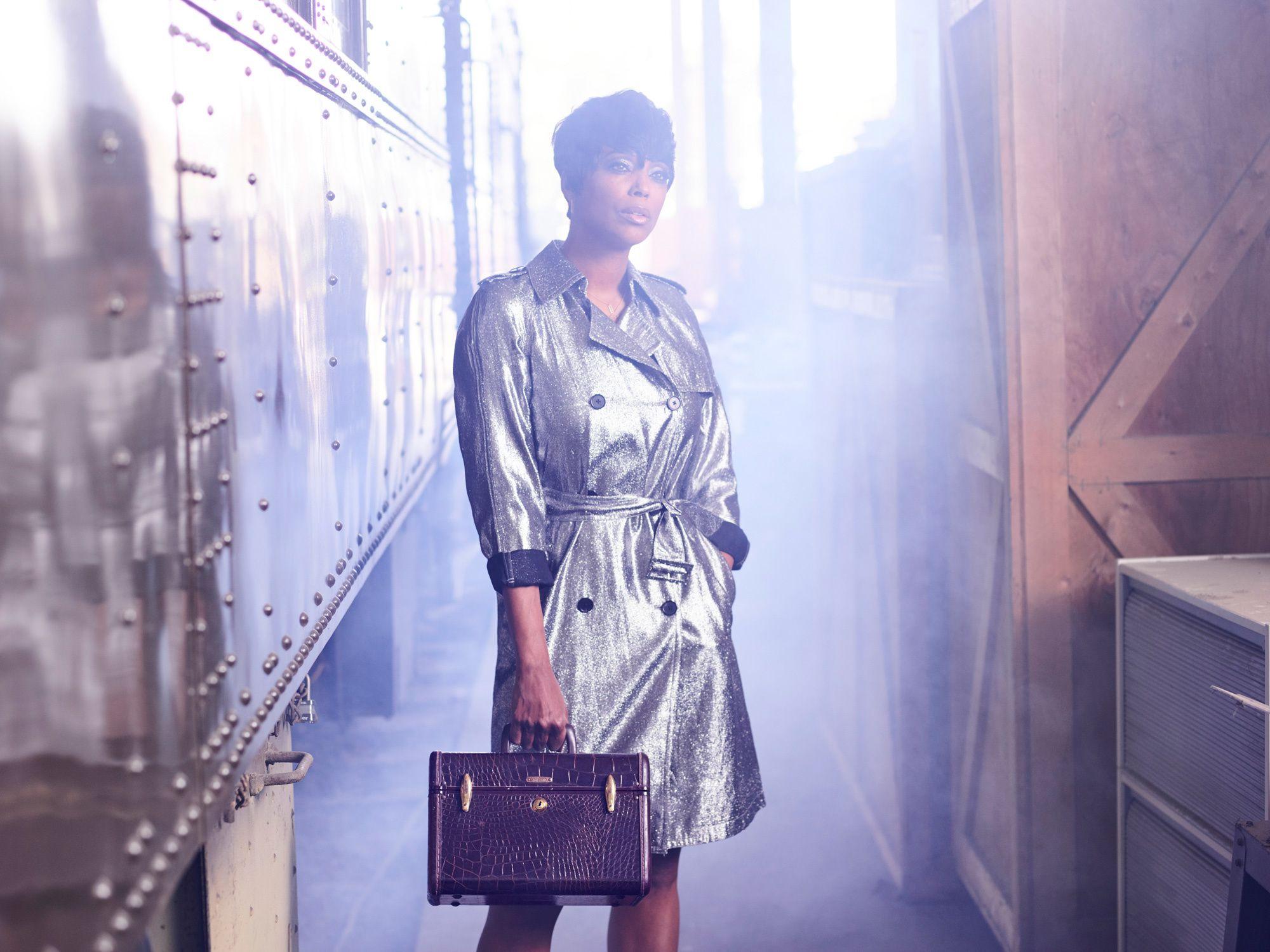 Aisha Tyler standing on train platform.