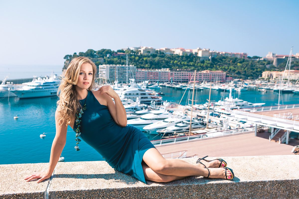 A.J. Cook lounging on her side, a marina in the backdrop.