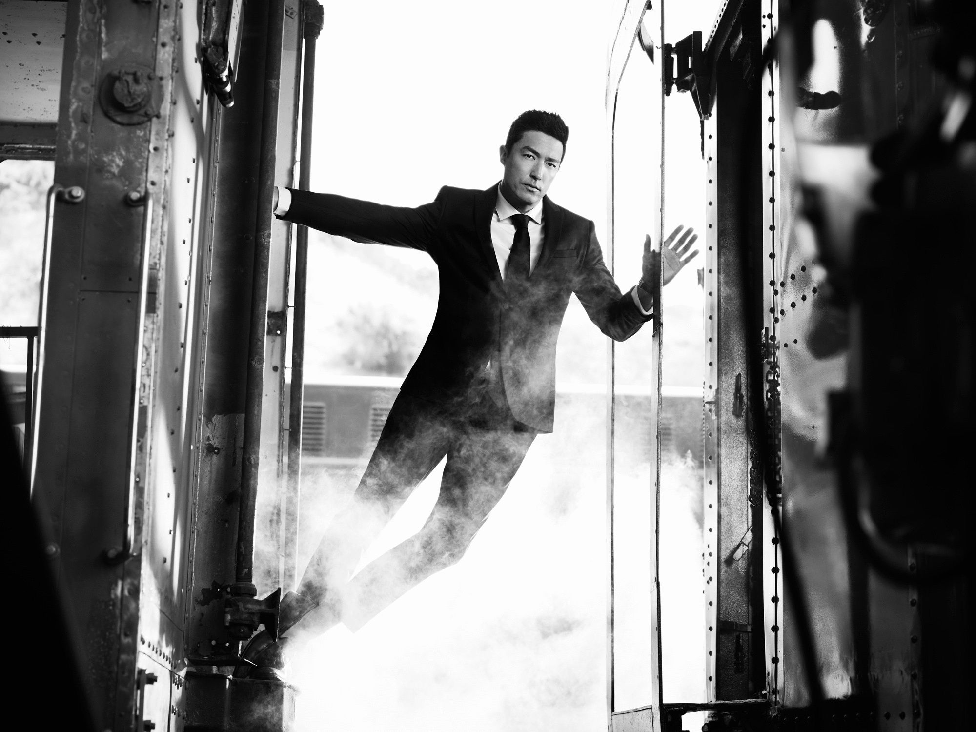Daniel Henney leaning out the back of a vintage train car.