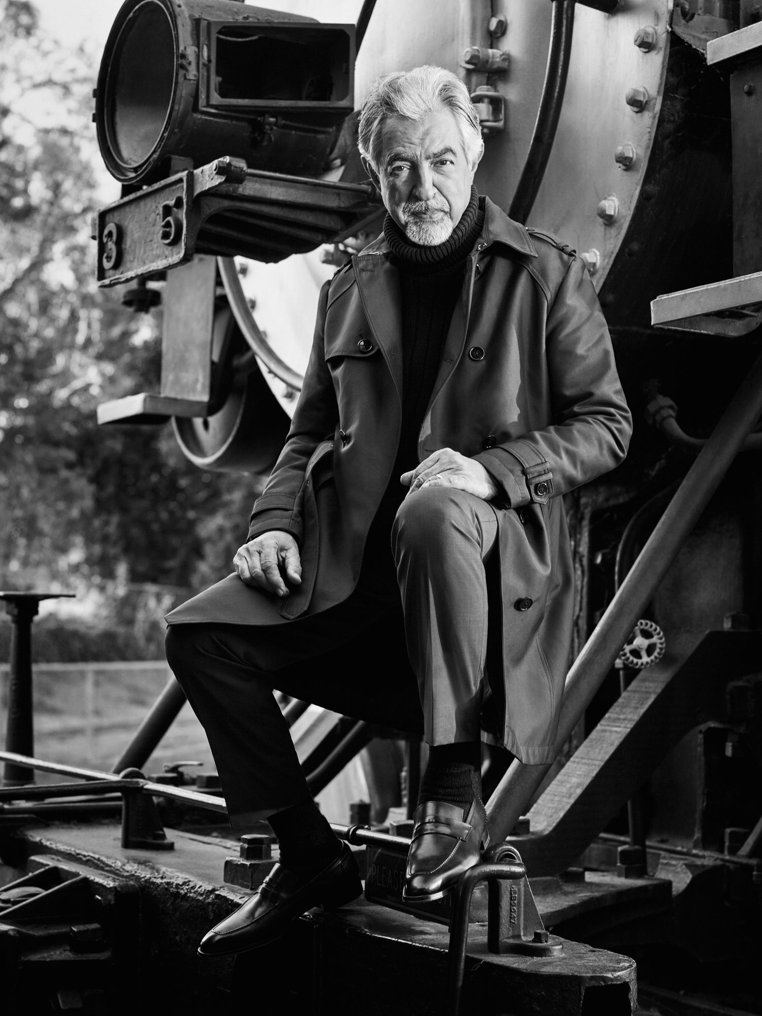 Joe Mantegna sitting in front of a vintage train locomotive.