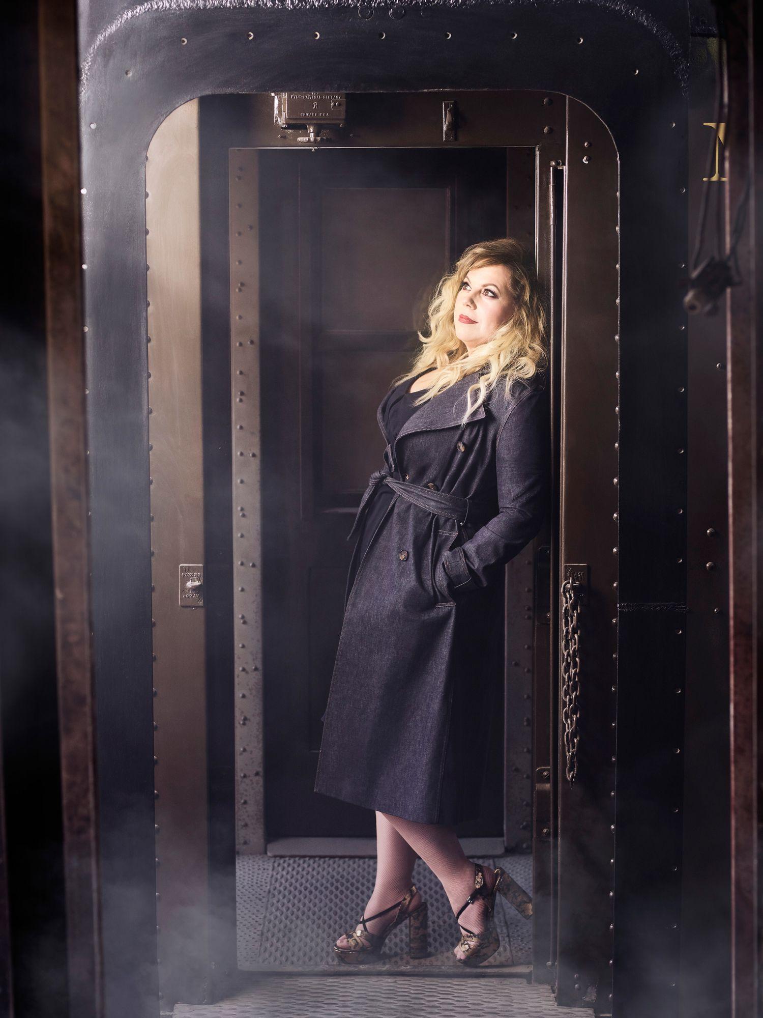 Kirsten Vangsness in black trench coat.