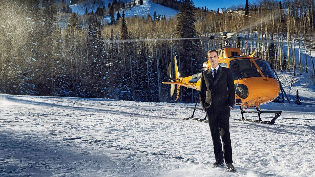 Matthew Gray Gubler in a black tux in the snow in front of helicopter.