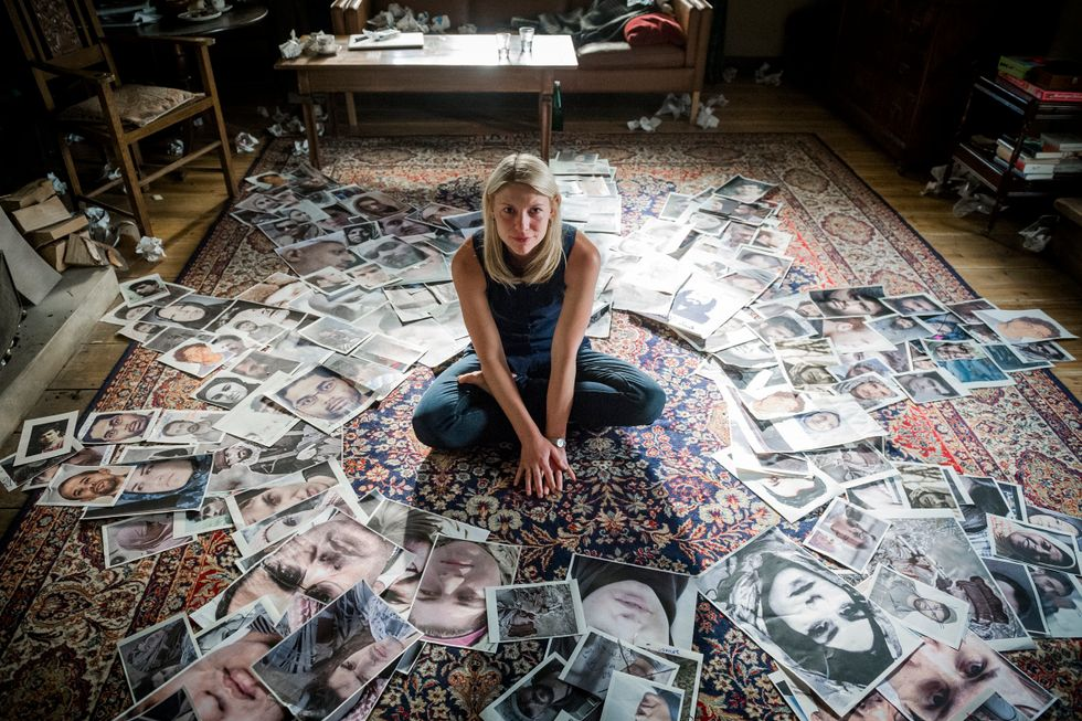 Claire Danes sitting on a pile of photographs.