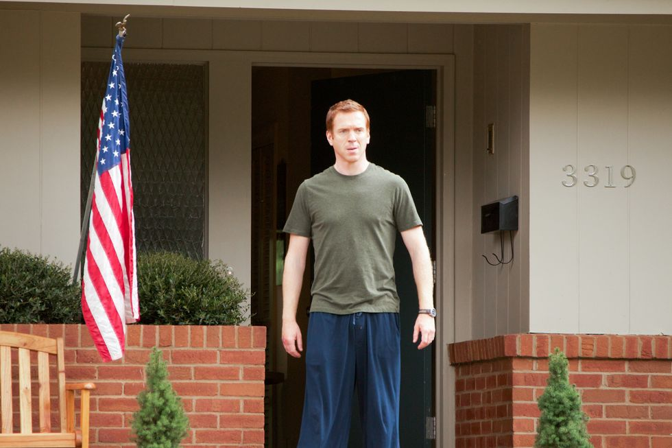 Damian Lewis standing outside home flying the American flag.