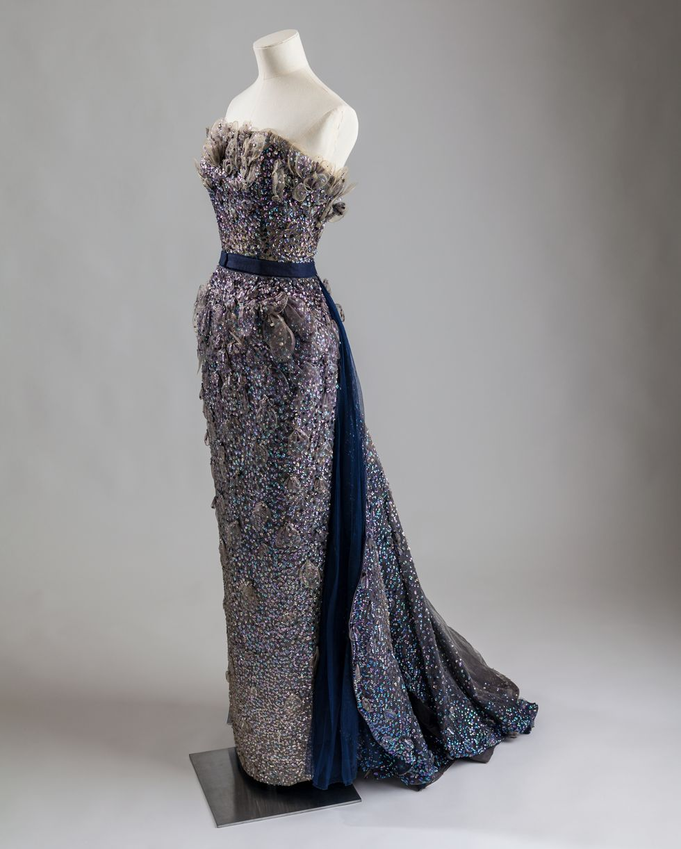 Mannequin wearing a navy jeweled strapless evening gown.