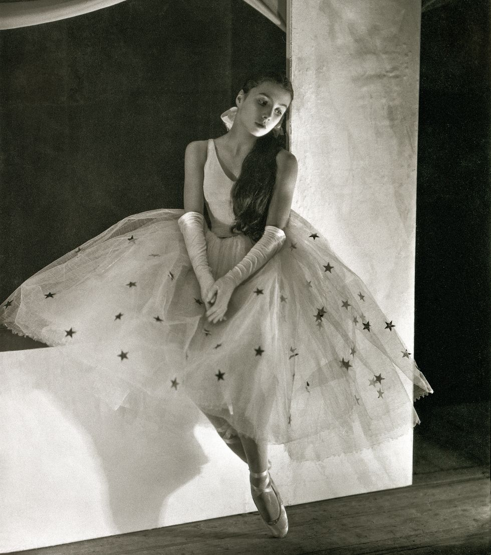 A black and white photo of Toumanova in a large tulle tutu covered in silver stars, white bodice and white gloves sitting on a large white set piece with her hands in her lap.