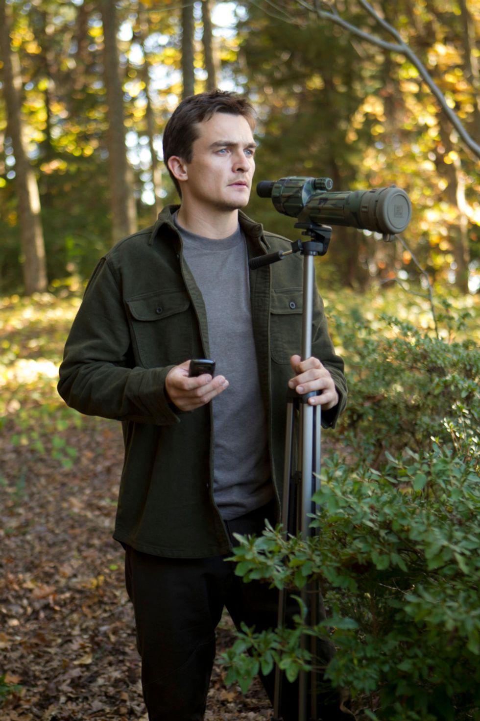 Rupert Friend behind a telescope in the woods.