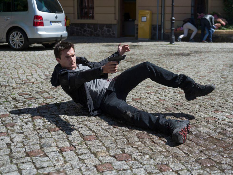 Rupert Friend lying on cobblestone street with a gun