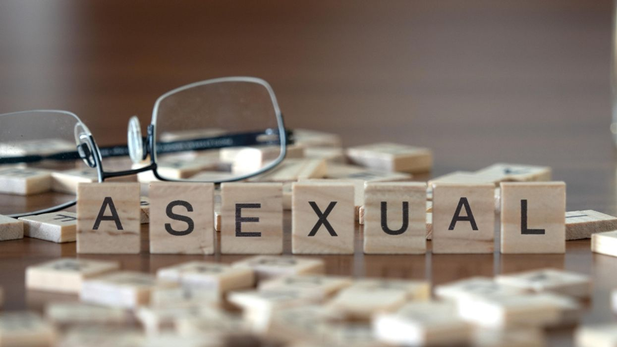 letter tiles spelling the word asexual with glasses on a desk