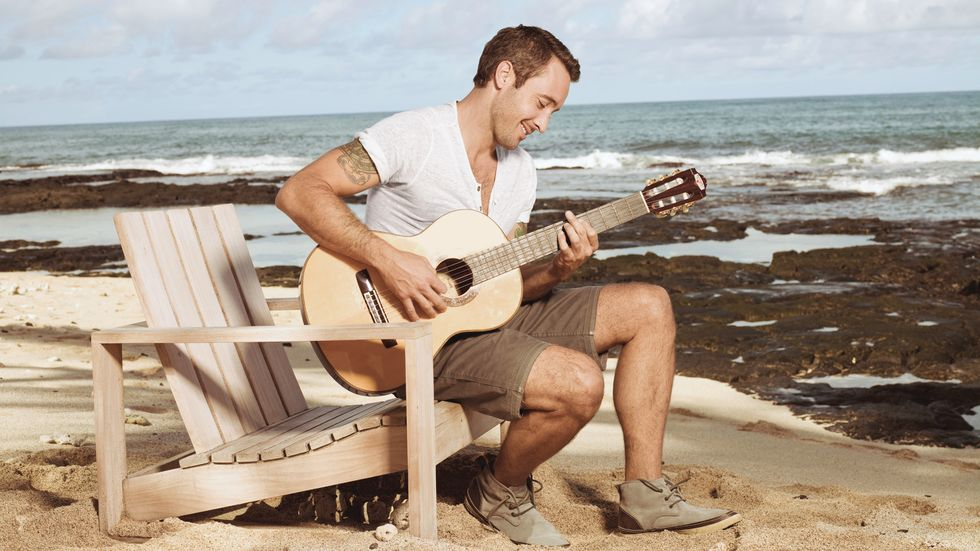 Alex O'Loughlin playing the guitar on the beach.