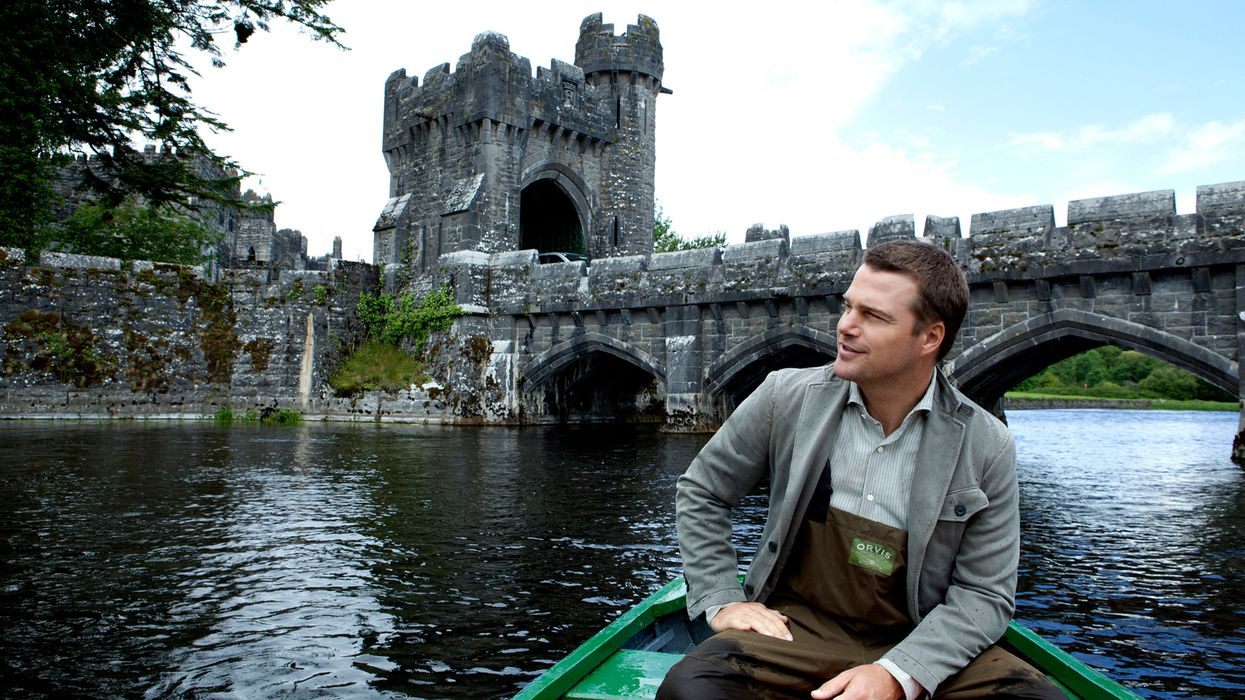 Chris O'Donnell rowing a boat in front of a castle.