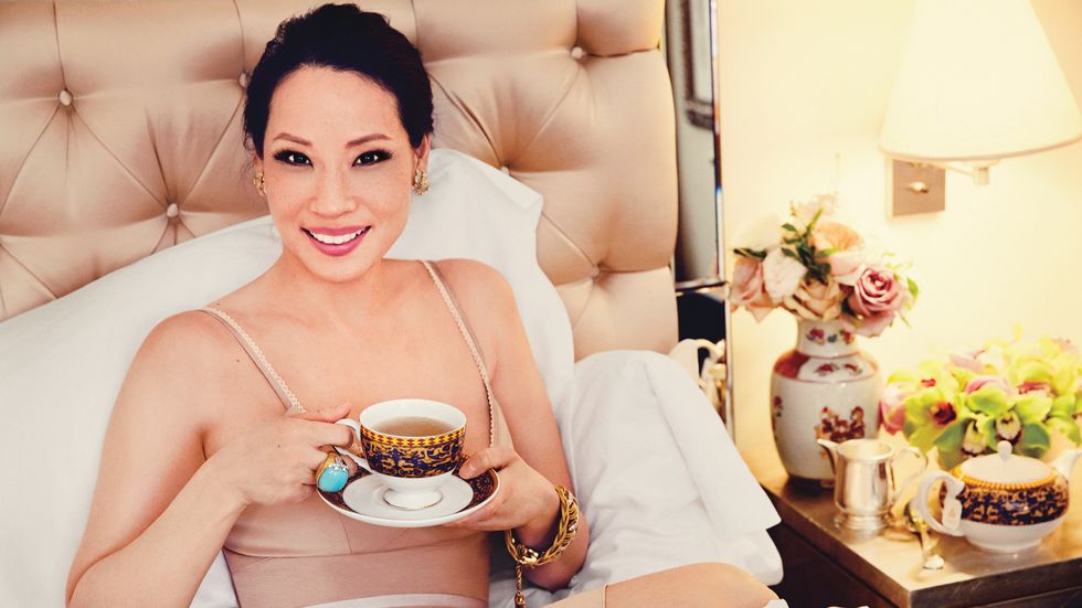 Lucy Liu drinking a cup of tea in bed.