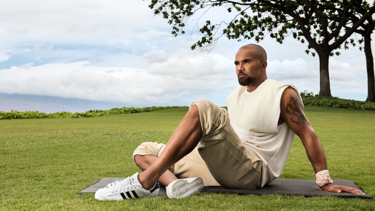 Shemar Moores sitting on a yoga mat.