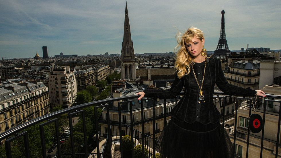 Beth Behrs posing in front of the Parisian skyline.