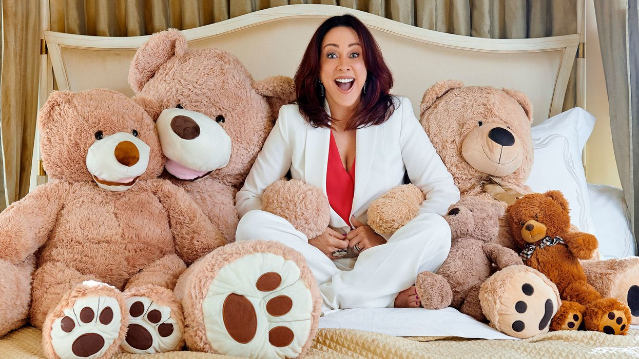 Patricia Heaton surrounded by lots of teddy bears.