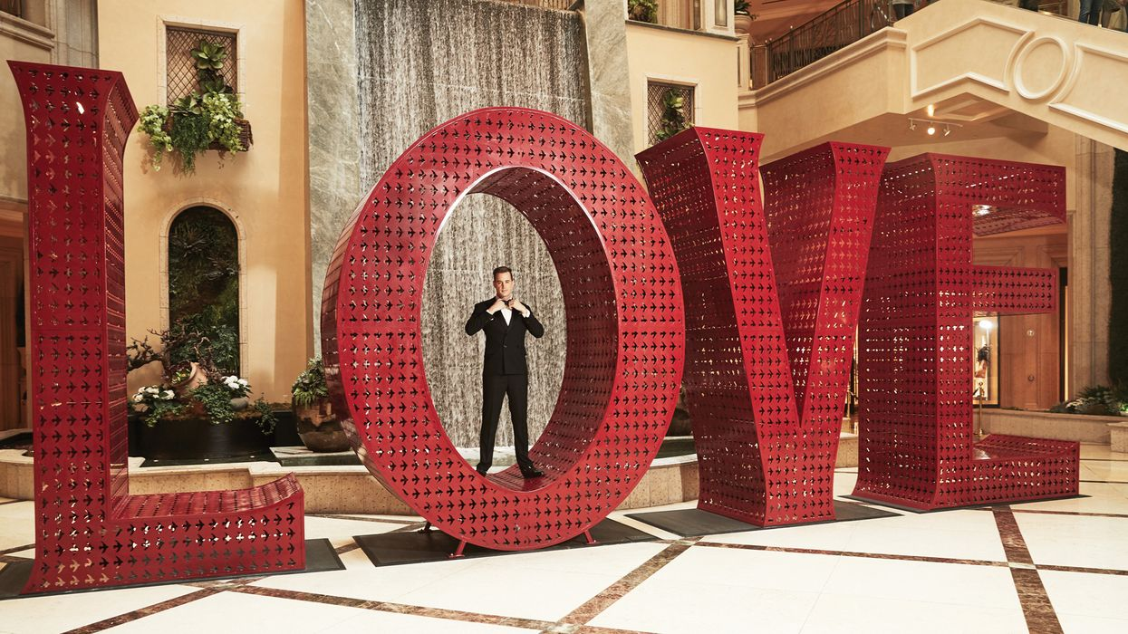 """Sean Murrray standing in the """"O"""" of the LOVE art installation."""