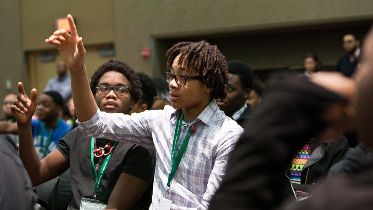 Black students raising their hands at a leadership conference