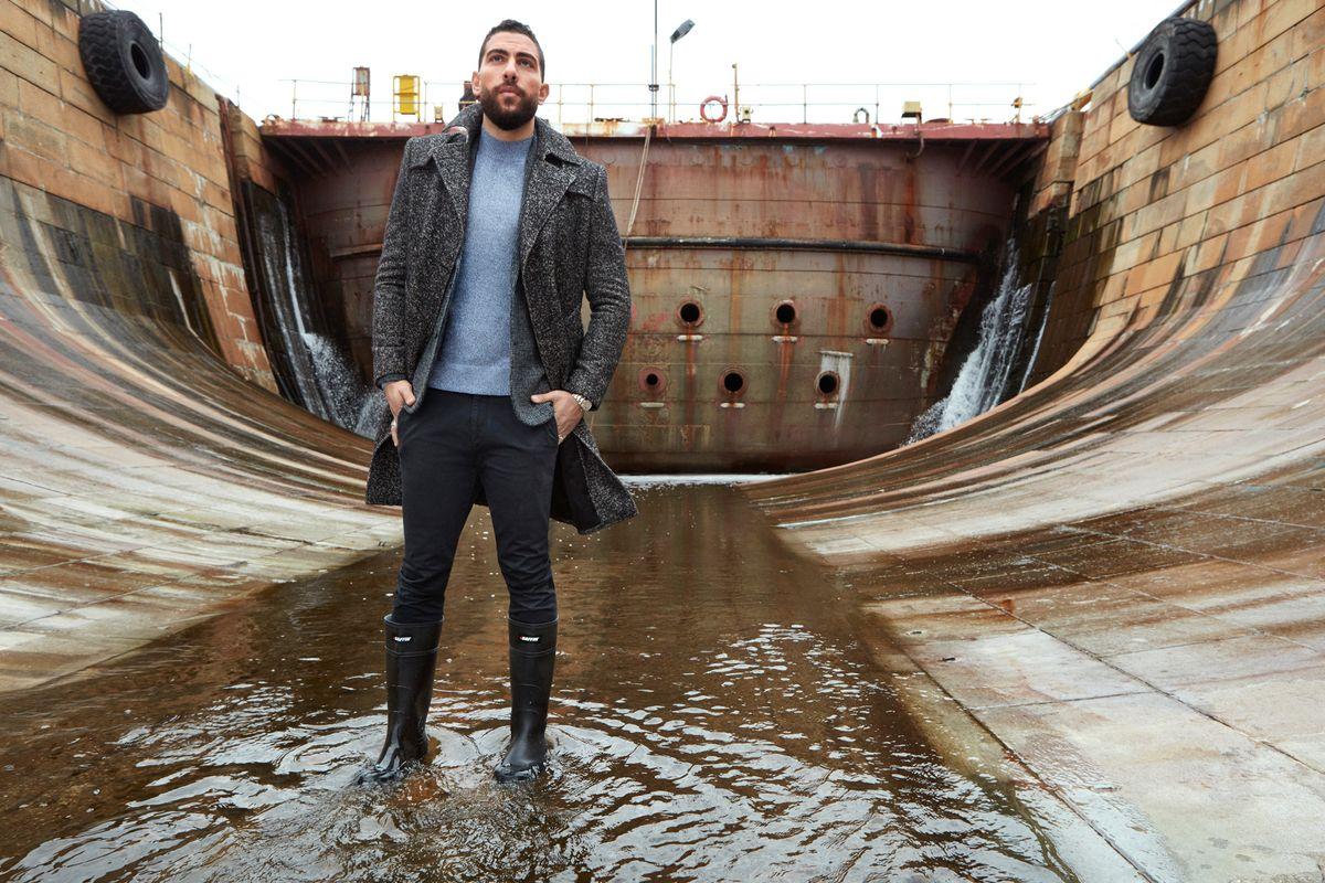 Zeeko Zaki standing in a puddle in belly of a ship.