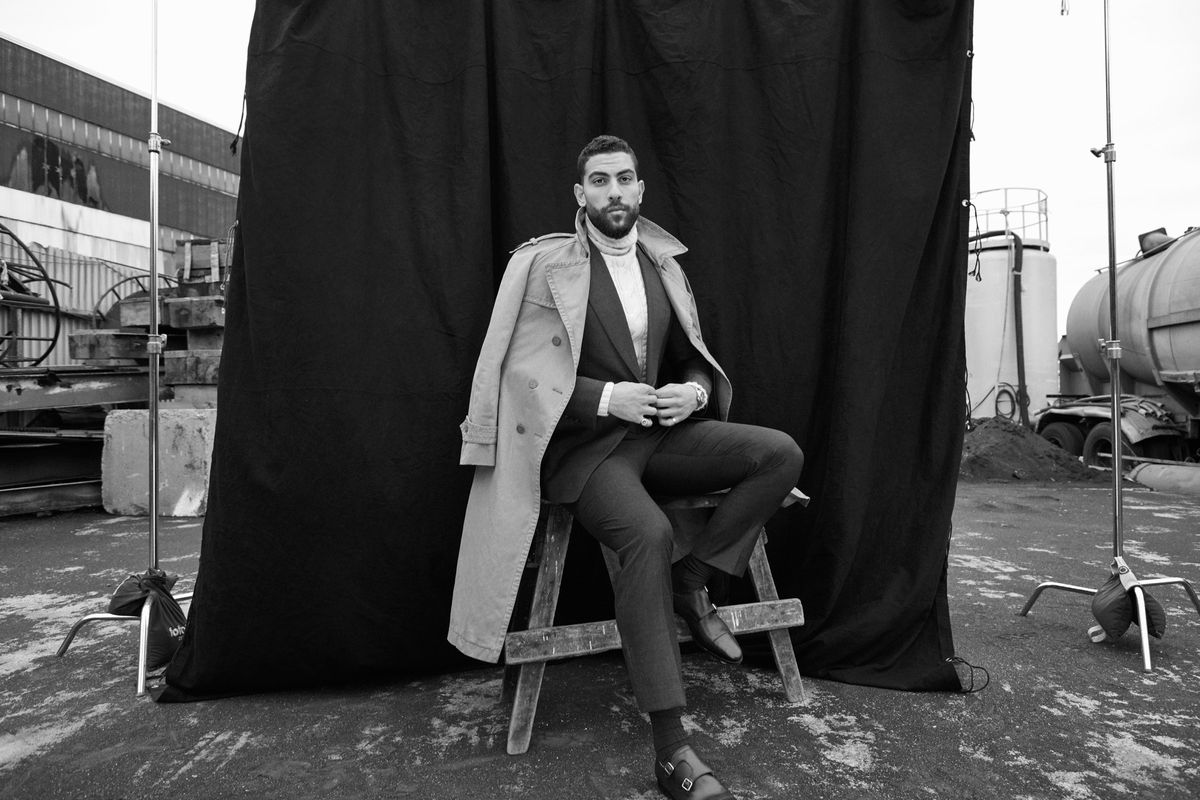 Black and white photo of Zeeko Zaki modeling a suit and trench coat.