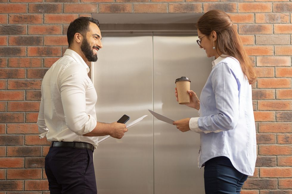 Two professionals flirt while waiting for the elevator