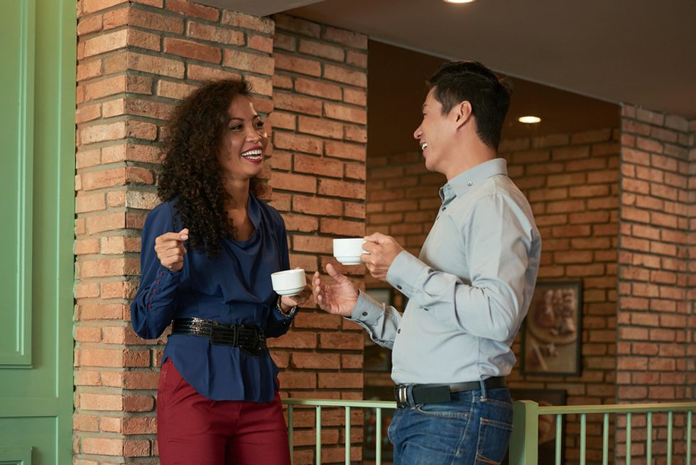Two co-workers flirt while on a coffee break