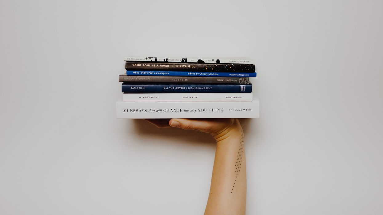 a hand holding a stack of books