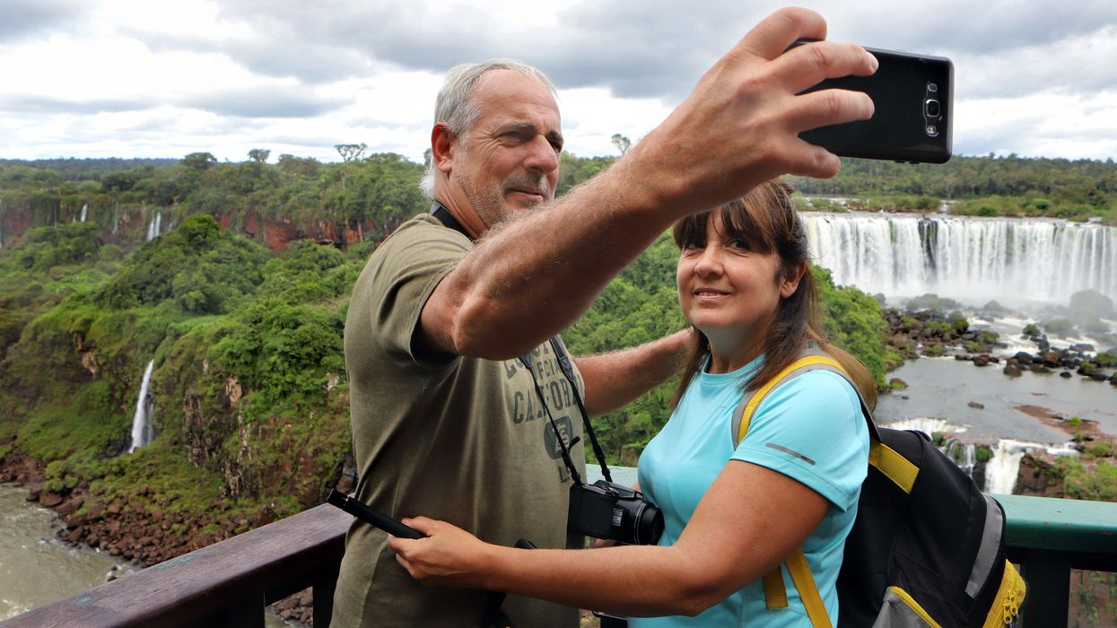 couple taking a selfie in front of a waterfall