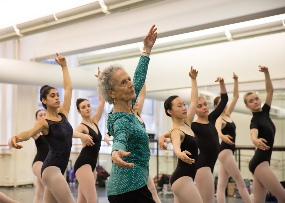Lupe Serrano, shown from the waist up and wearing a long-sleeved green shirt and black pants, demonstrates tendu crois\u00e9 devant. A group of teenage dancers in lack leotards and pink tights stand behind and to the right of her, imitating her position.