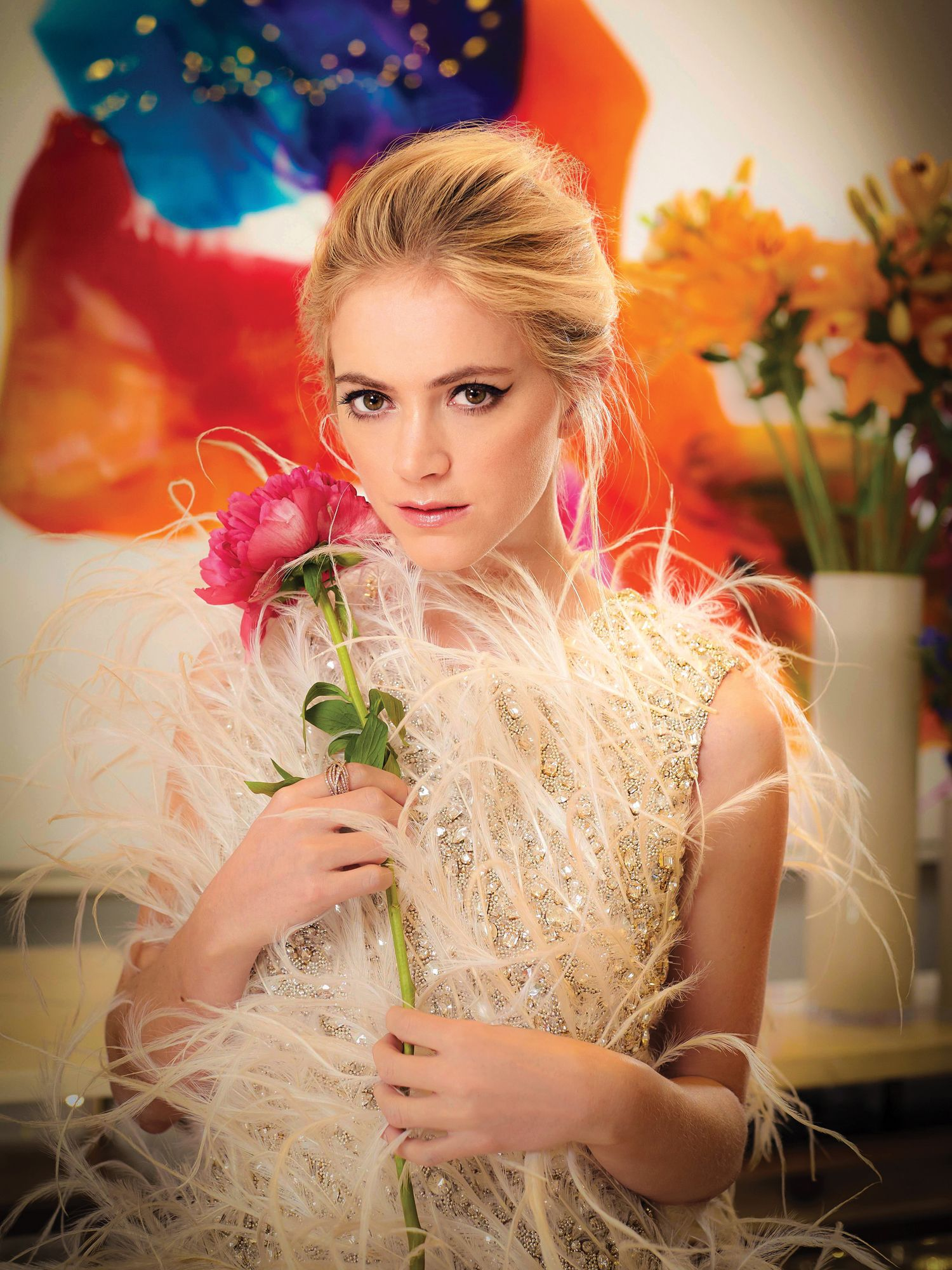 Emily Wickersham holding a pink rose and wearing a feathered designer gown