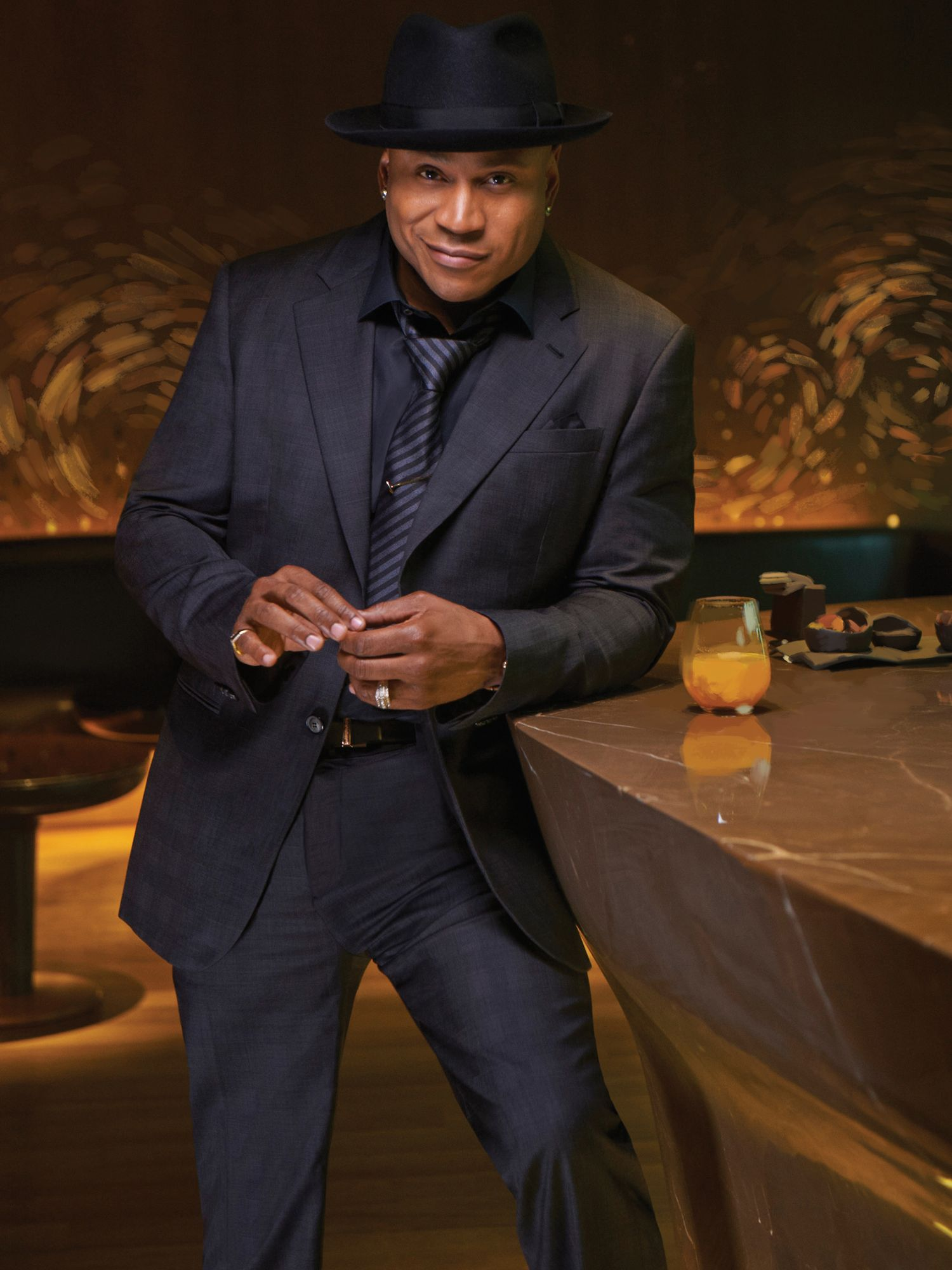 LL COOL J of NCIS Los Angeles smiling in black on black tuxedo with hat