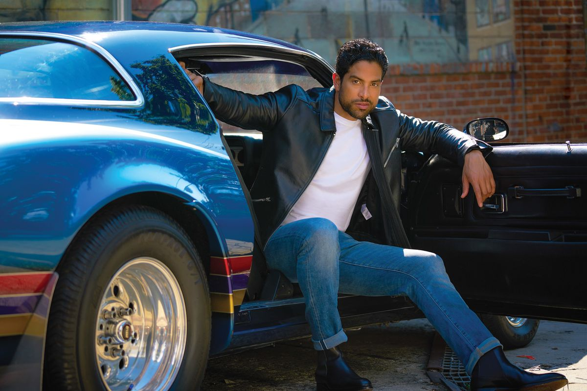 Adam Rodriguez of Criminal Minds in leather jacket with blue sportscar