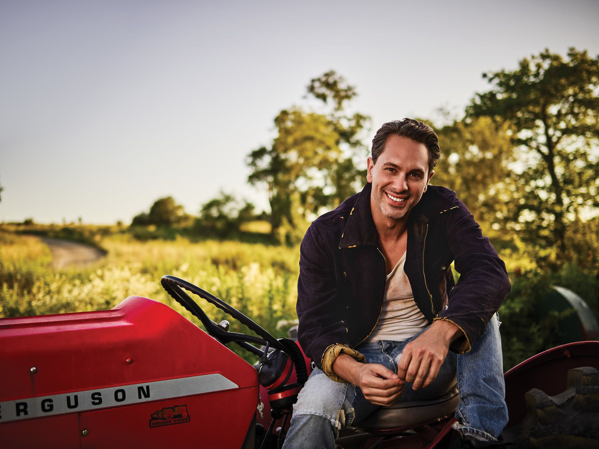 Thomas Sadoski in jeans on a tractor
