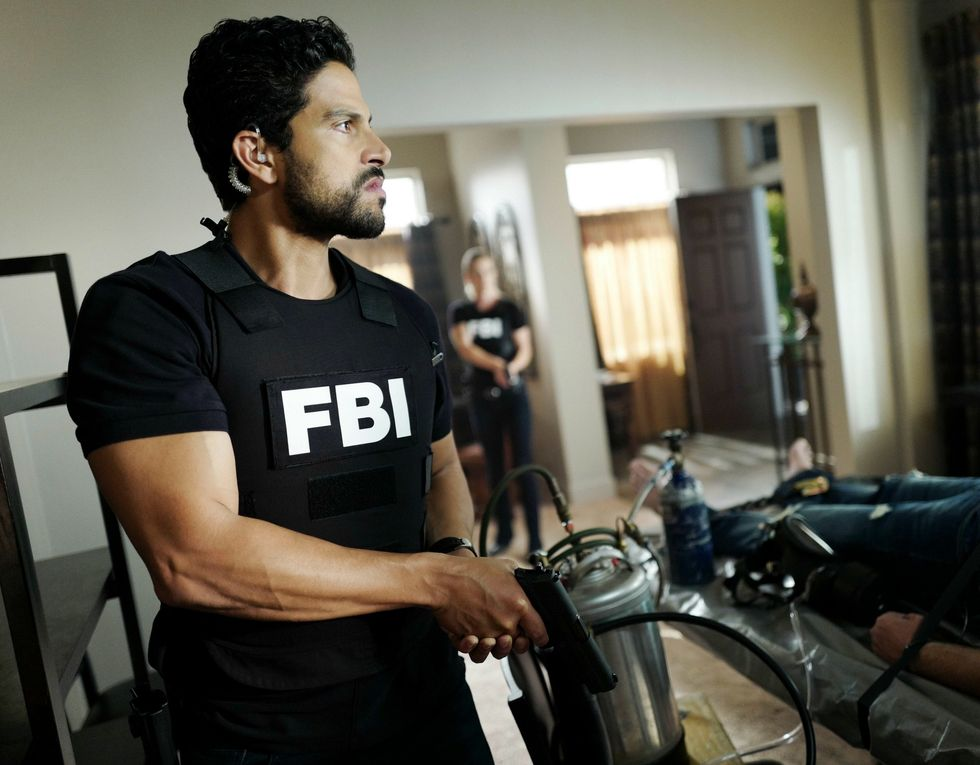 Alex Rodriquez as his character Eric Delco wearing a FBI uniform and holding a gun pointed down