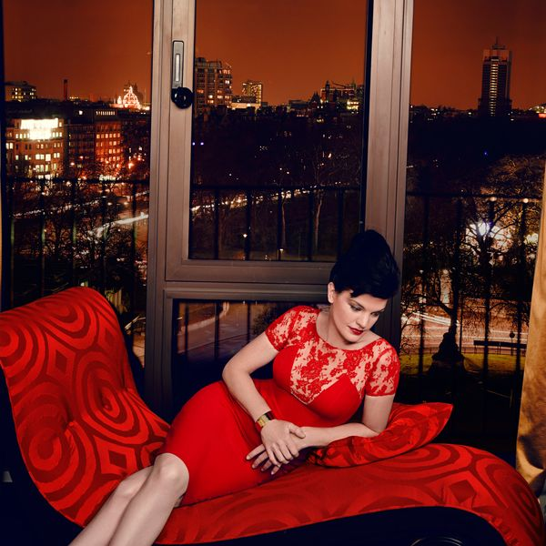 Pauley Perrette in a red dress sitting on a red sofa.