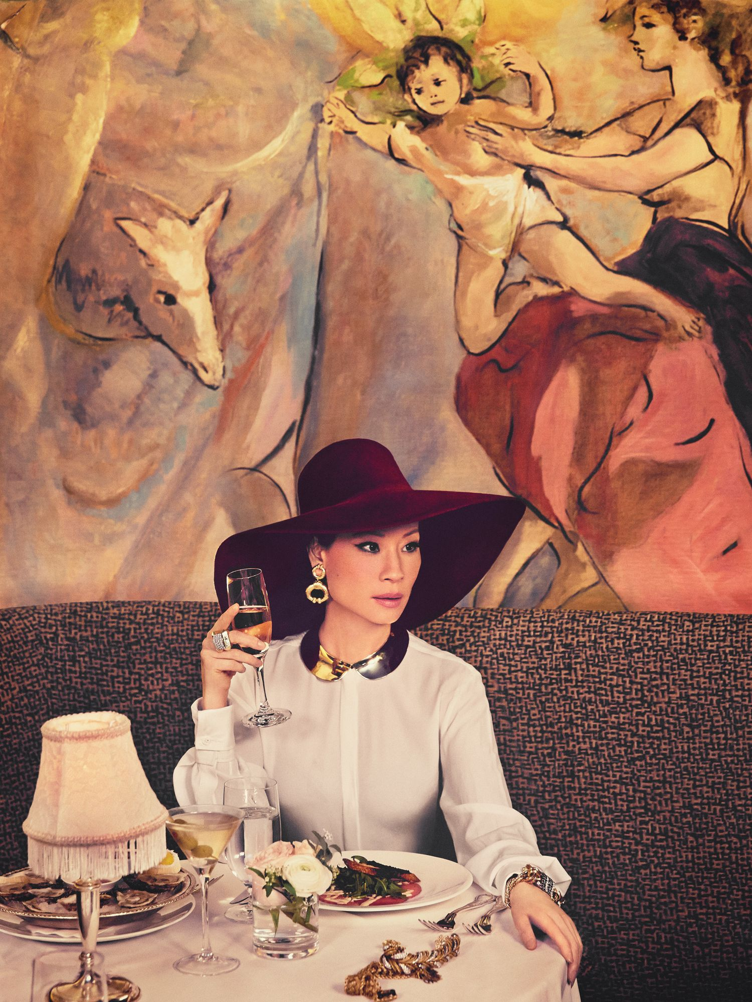 Lucy Liu of Elementary in red floppy hat drinking champagne