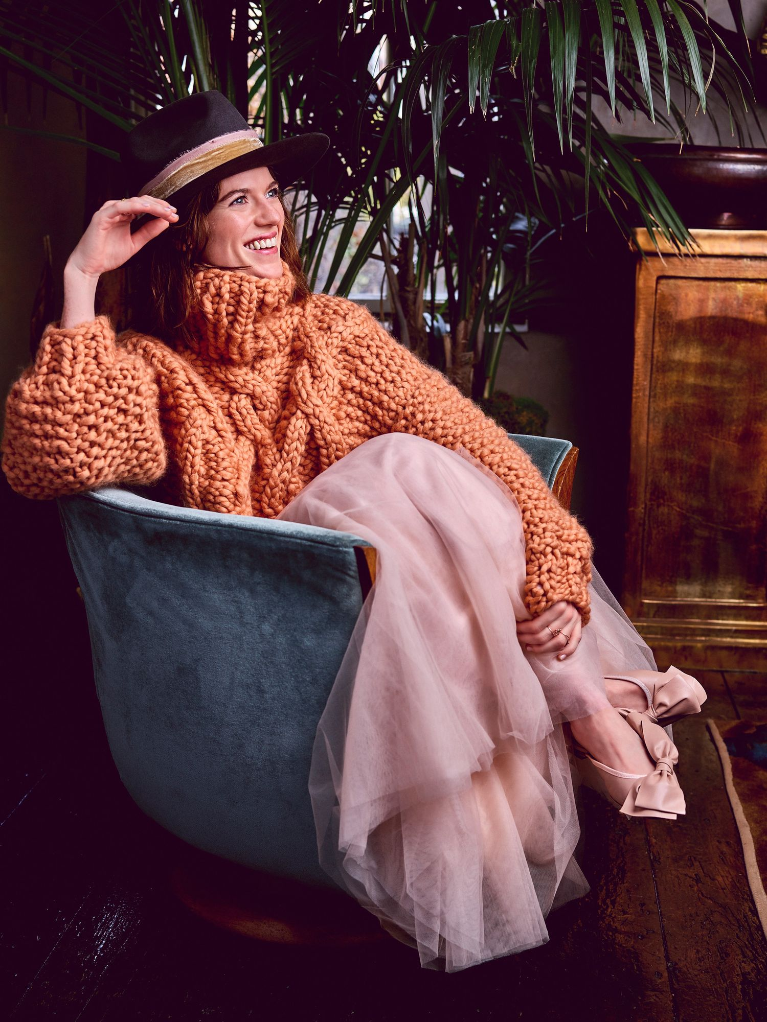 Rose Leslie of The Good Fight in chunky orange sweater and hat