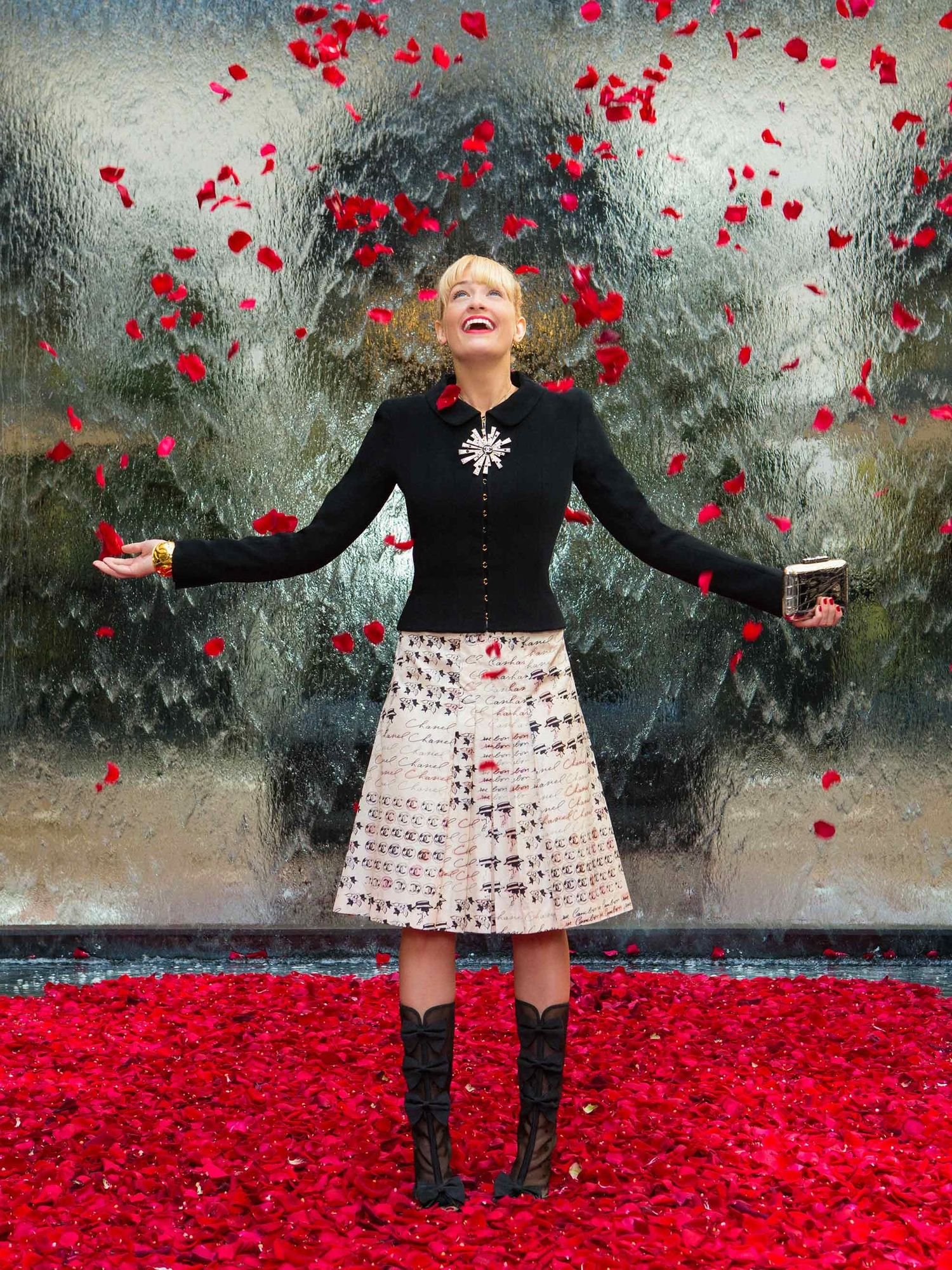 Beth Behrs of The Neighborhood with falling rose petals.