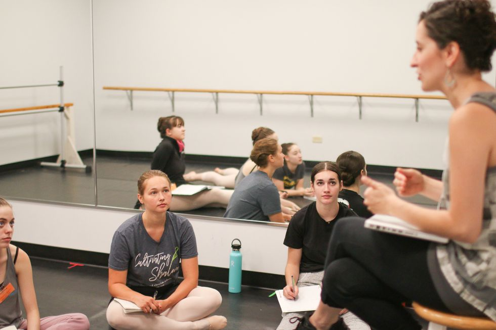 Three young dancers sit crosslegged on a dance studio floor, wearing casual T-shirts and pink tights and shoes. A faculty member sits on a chair in front of them leading a discussion with a laptop on her lap; she wears dark leggings and a gray, loose-fitting tank top.