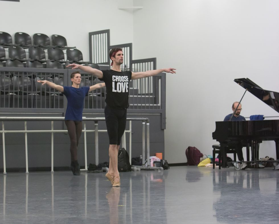 Two male dancers in practice clothes stand in sous-sus with their arms out in second position