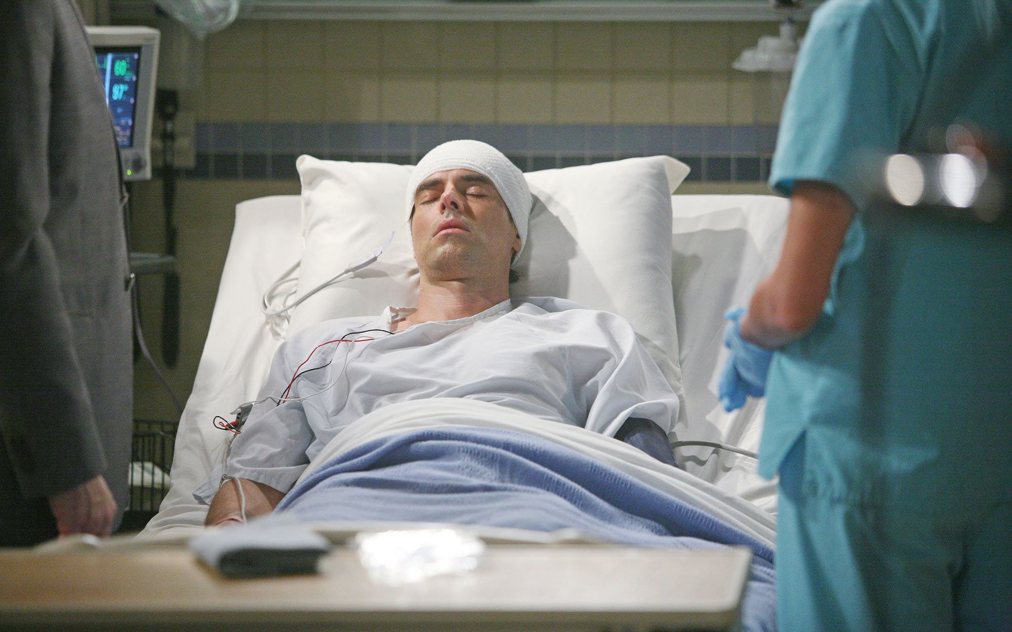 Jason Thompson laying in a hospital bed for a scene in The Young and the Restless.